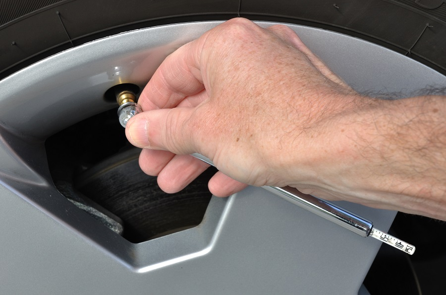 checking tire pressure with a stick gauge