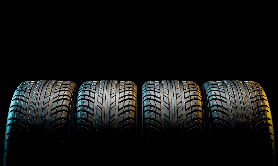 Four Matching Tires on Black Background