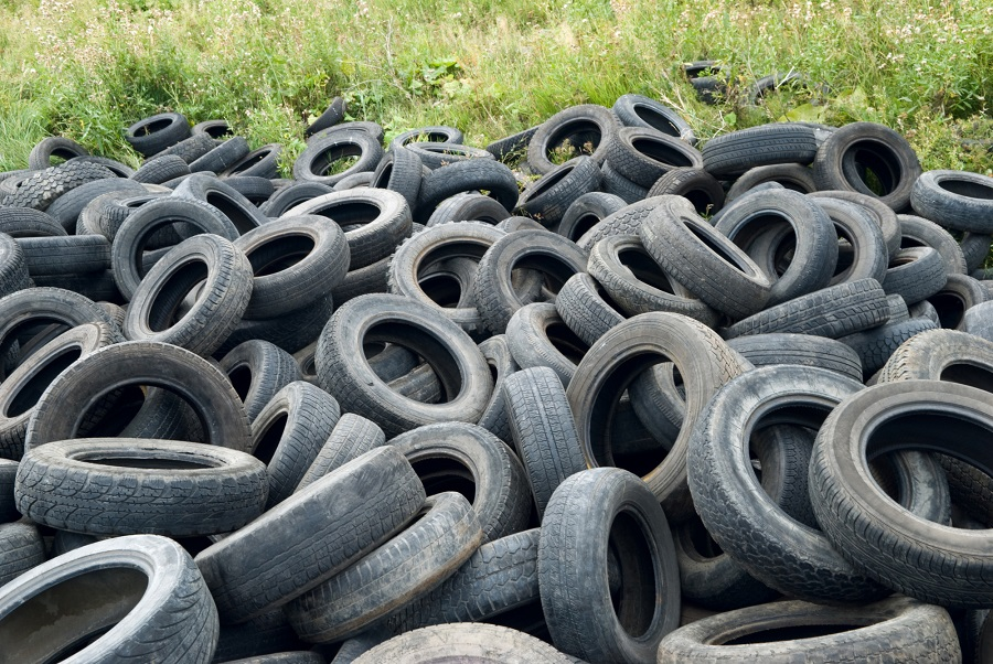 piles of old tires in a field