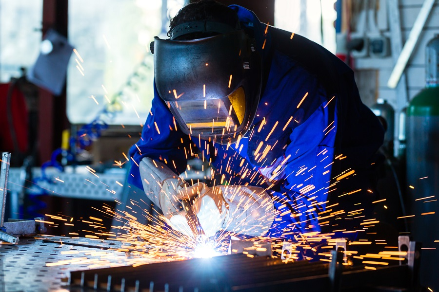 Welder welds with sparks using an auto darkening welding helmet