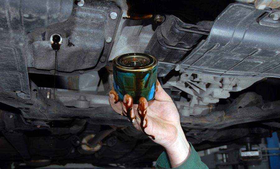 mechanic doing an oil change old oil filter