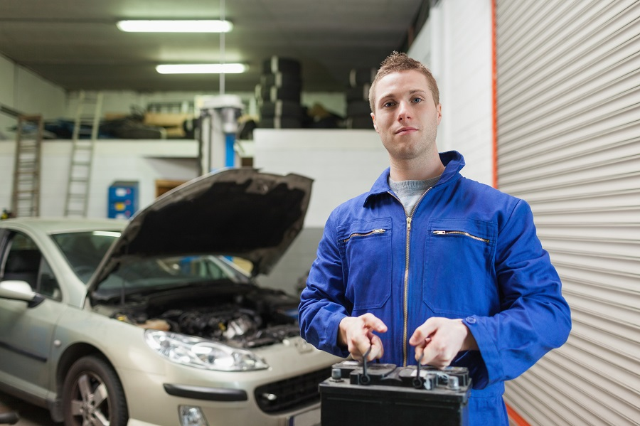mechanic returning a car battery
